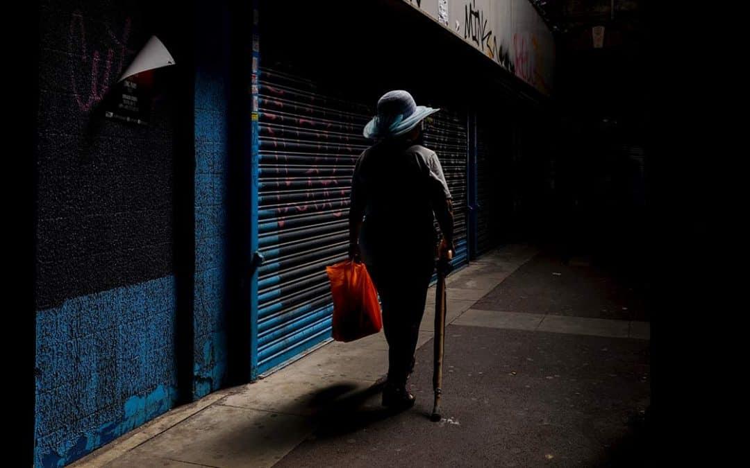 Woman walking down dark street.