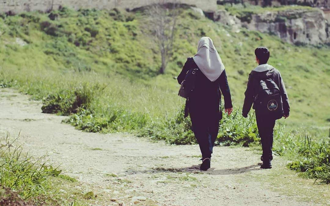 A mother and her son walking to a village