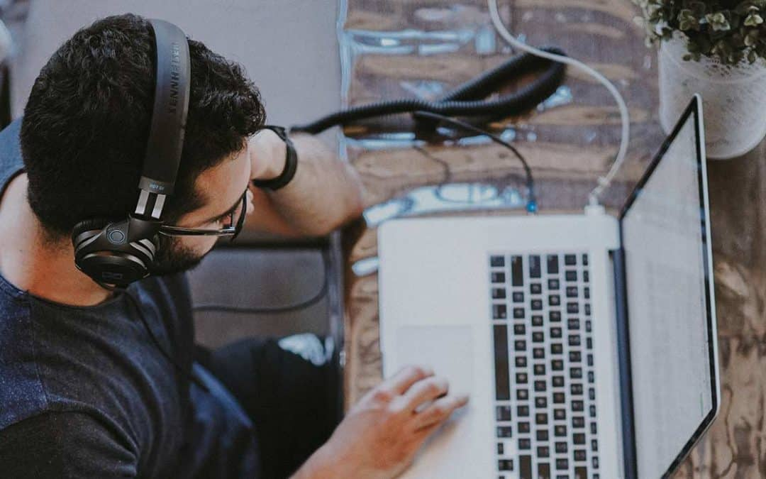 Man listening on head phones and using computer